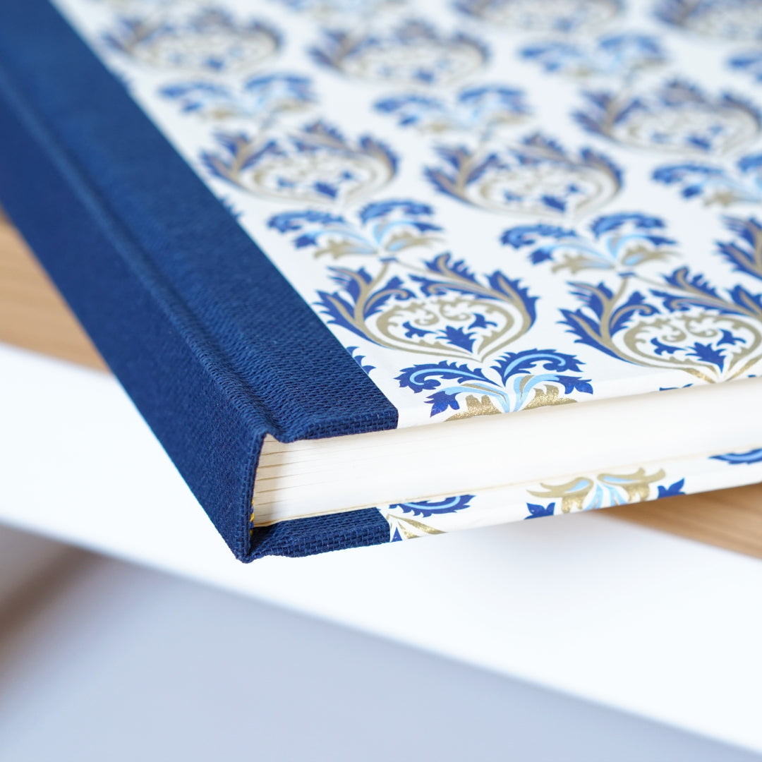 corner of a blue spined notebook with a regal gold and blue pattern