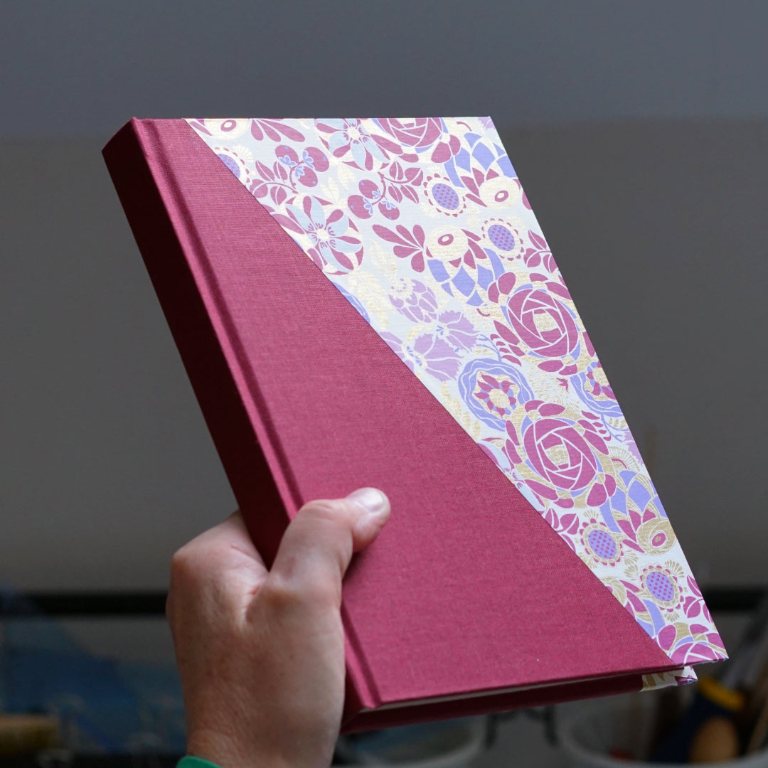 hand holding floral notebook with diagonal overlay of book cloth
