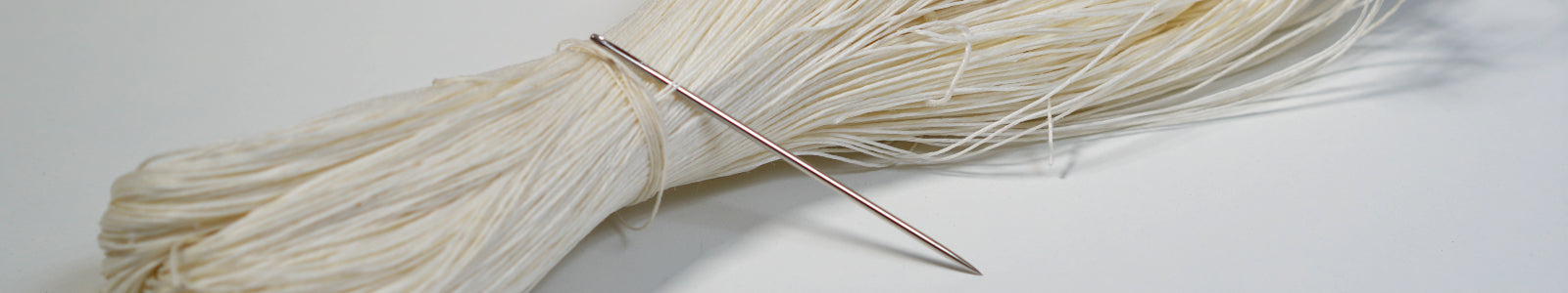 bundle of thread with needle going through