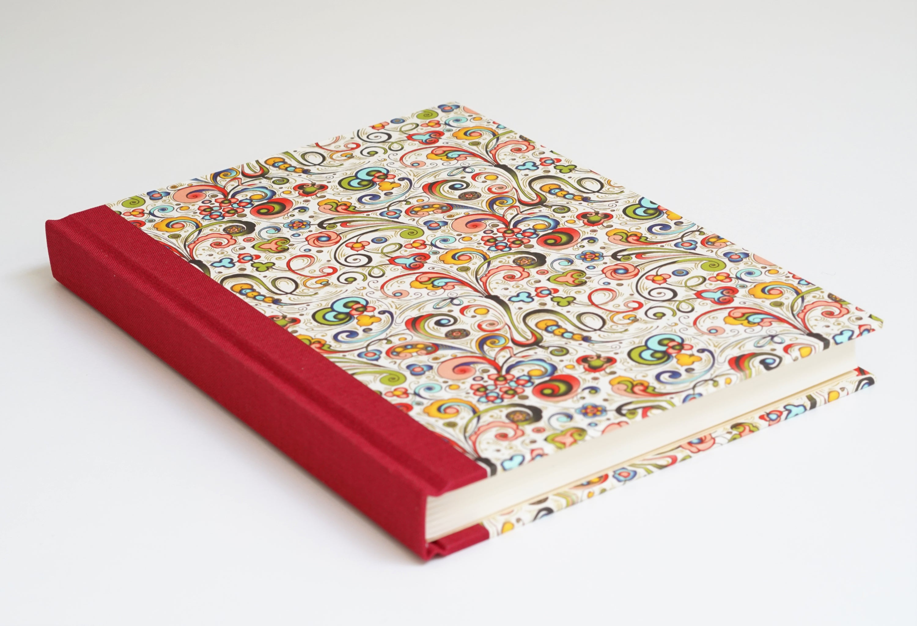 red spined notebook with colourful red floral pattern