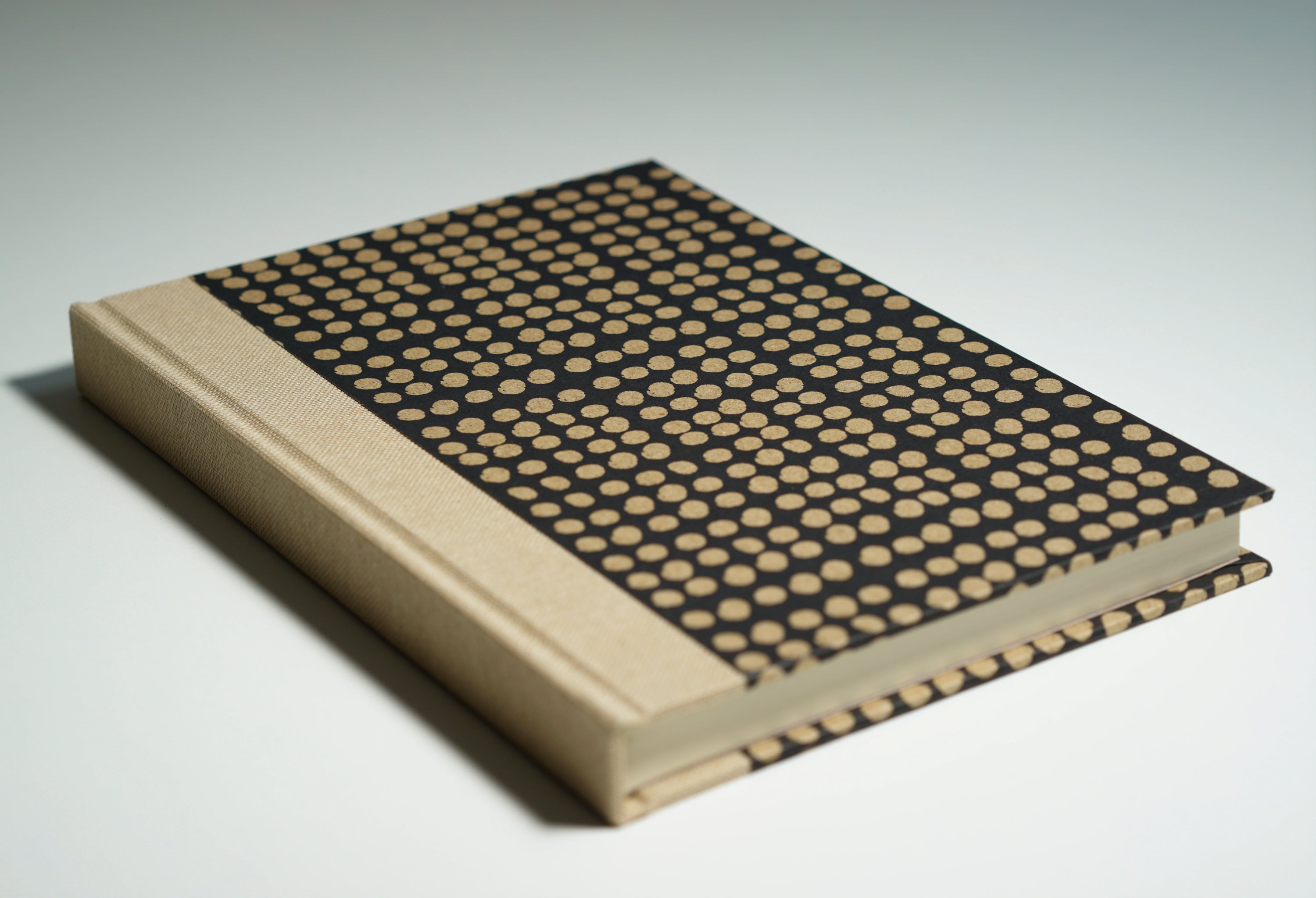 black notebook with oatmeal spine and oatmeal dotted pattern