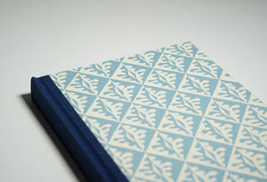 top half of a blue notebook with tiled leaf pattern