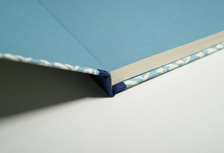 open blue notebook with a close up of the spine