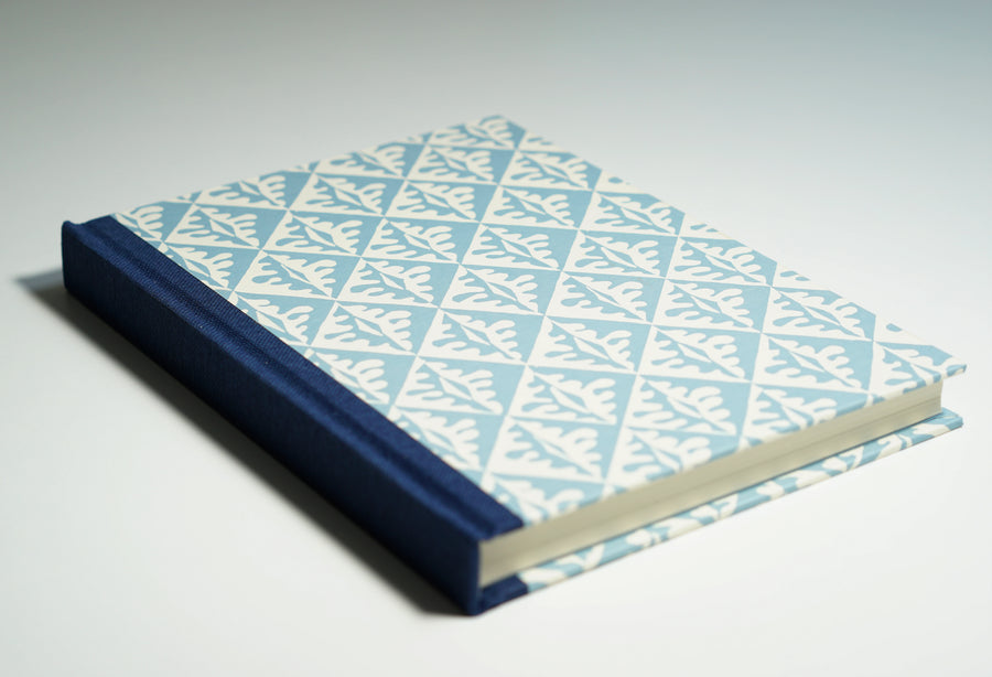 blue notebook with tiled leaf pattern lying flat