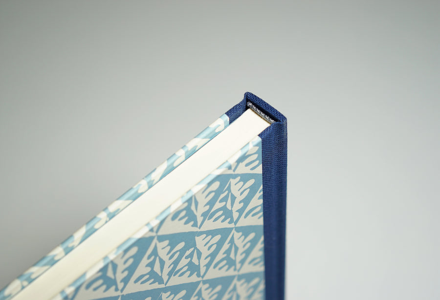 top of a blue notebook with tiled leaf pattern