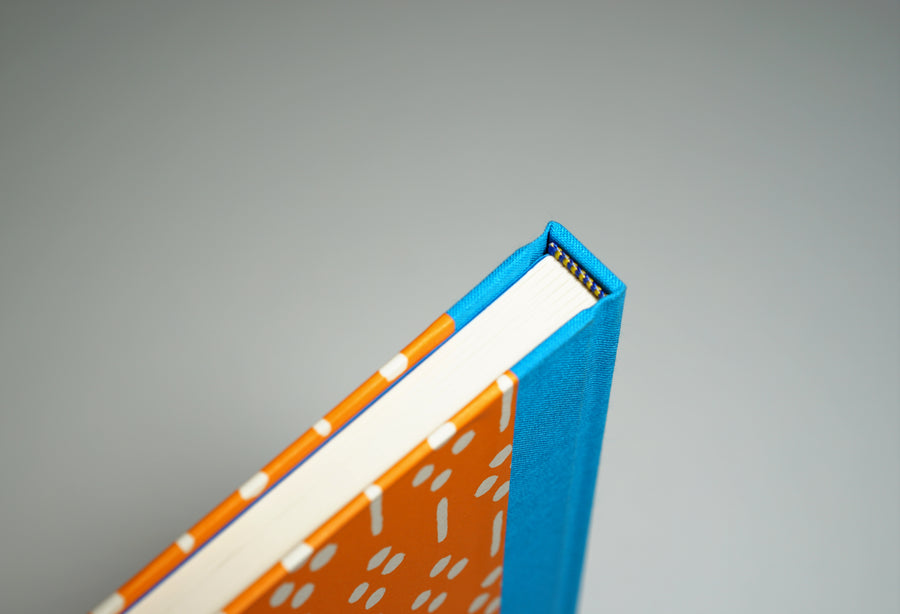 top of spine of a bright orange notebook
