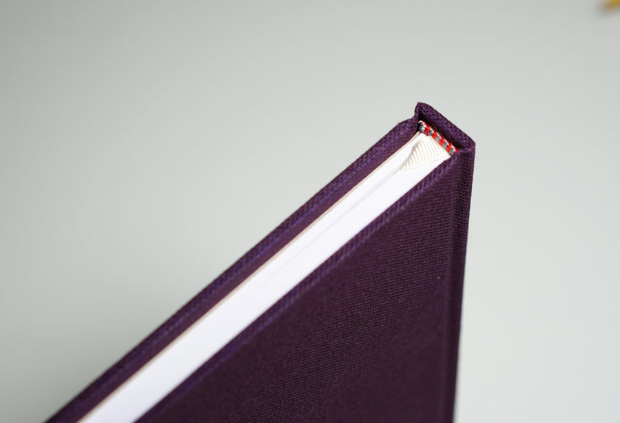 top of spine of a deep purple fabric notebook