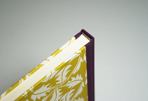 spine from top of a yellow leaf patterned notebook