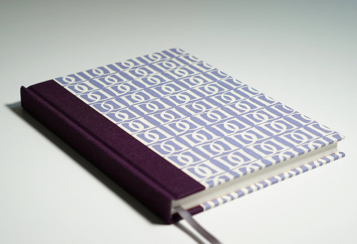 purple notebook with white d pattern lying flat
