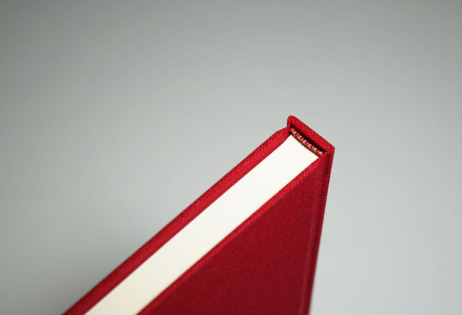 spine from top of a red linen fabric notebook