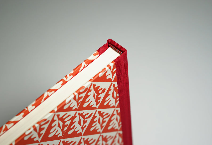 top of spine of a red tile patterned notebook