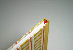 top of spine on top of a yellow patterned notebook with red accents