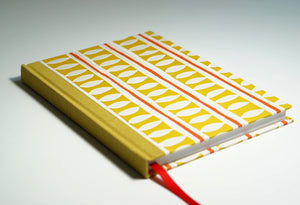 yellow patterned notebook with red accents lying flat