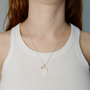 Hunt Of Hounds Pegasus Necklace. Coin pendant necklace with pegasus and stars. Sunstone charm with wings. On model.