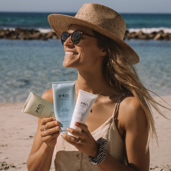 Smiling woman, walking on the beach, holding 3 tubes of People4Ocean sun cream in her hand