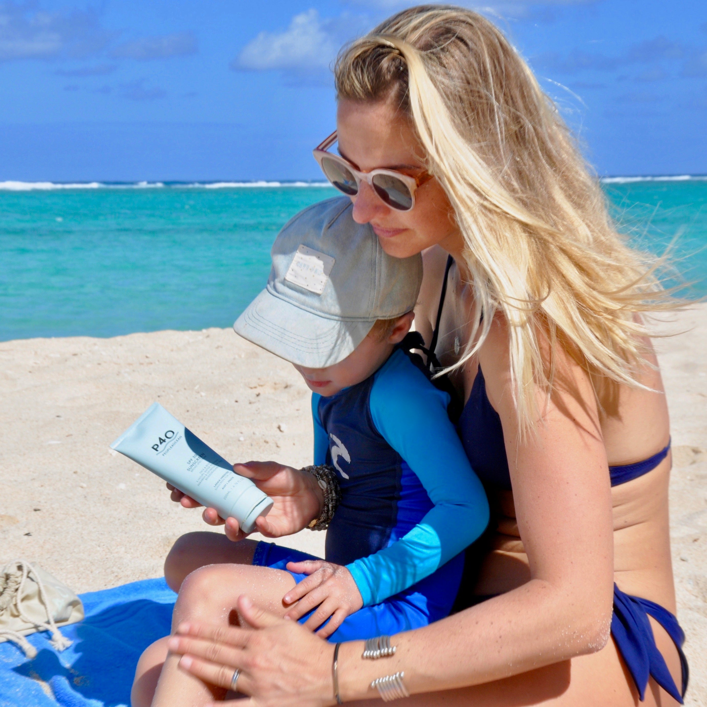 Mother applies People4Ocean SPF30 sunscreen to child at the beach