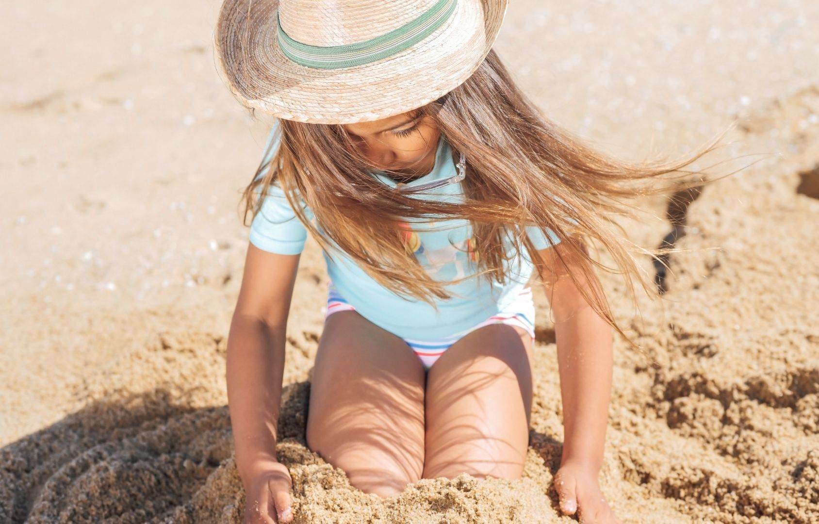 Girl sitting on the sand in sunscreen and a hat
