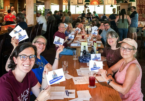 A group of postcard writers at a table, holding up postcards