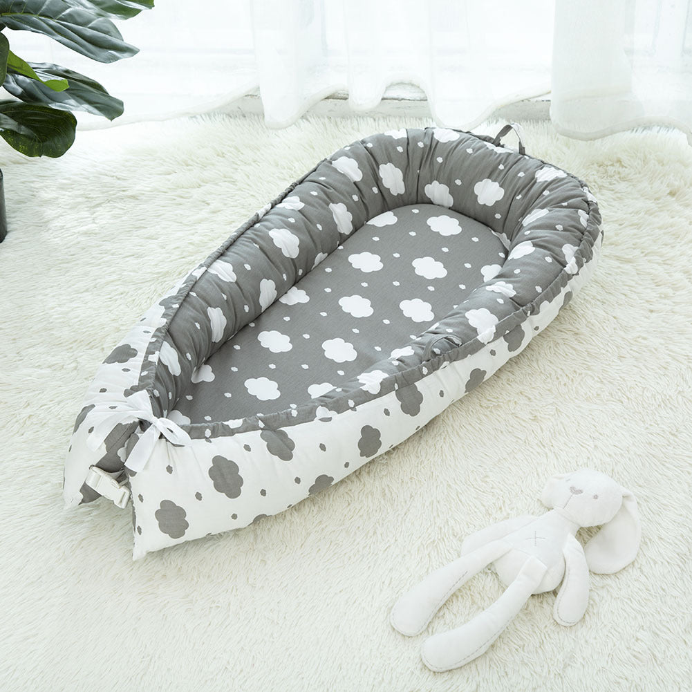 Grey portable baby crib with white clouds