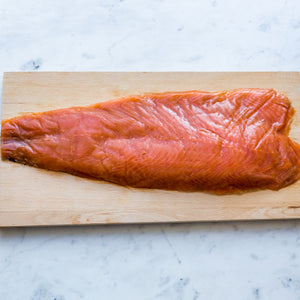 1kg side of sliced smoked salmon served on wood board on marble surface