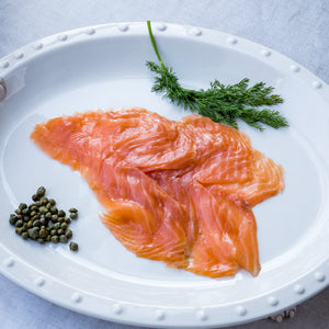 Sliced smoked salmon on white serving plate with fresh dill and capers
