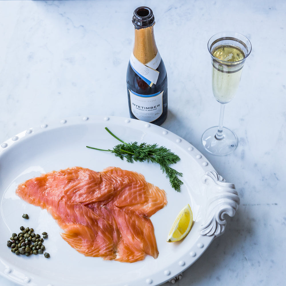 Sliced smoked salmon on white serving plate with fresh dill, caper and lemon segment, with English sparkling wine bottle and flute