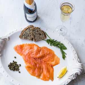 Sliced cold smoked salmon served on white plate with seeded bread, fresh dill, lemon segment and capers, on marble service with English sparkling wine bottle and flute