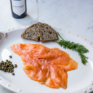 Sliced smoked salmon on white serving plate with seeded bread, fresh dill and capers, with English sparkling wine bottle and flute