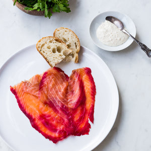 Sliced beetroot and gin infused smoked salmon on white plate with sourdough bread, on marble surface with horseradish sauce and teaspoon and flat leaf parsley