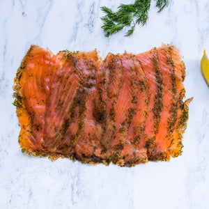 Sliced gravadlax on marble surface with fresh dill and lemon segment