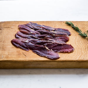 Sliced smoked venison with cracked black pepper on wooden board with rosemary