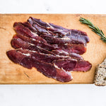 Sliced smoked venison with cracked black pepper on wooden board with seeded bread and rosemary
