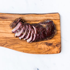 Sliced hot smoked goose breast served on wooden board on marble surface