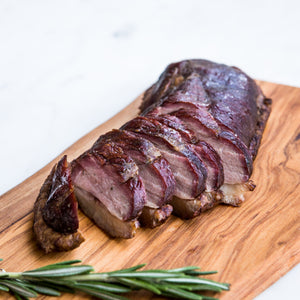 Load image into Gallery viewer, Sliced hot smoked goose breast served on wooden board with rosemary