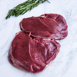 Venison haunch steaks on marble surface with rosemary