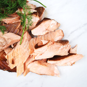 Load image into Gallery viewer, 1kg side of hot smoked salmon, flaked on marble surface with fresh dill