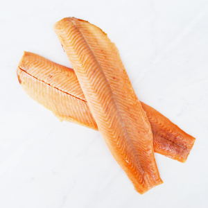 Two hot smoked trout fillets on marble surface