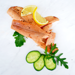 Flaked hot smoked trout fillets on marble surface with fresh lemon, cracked black pepper, rocket and cucumber slices