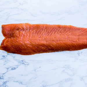 1kg side of sliced cold smoked salmon on marble surface