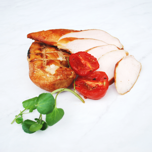 Sliced hot smoked chicken breast on marble surface with halved, roasted tomatoes and fresh watercress