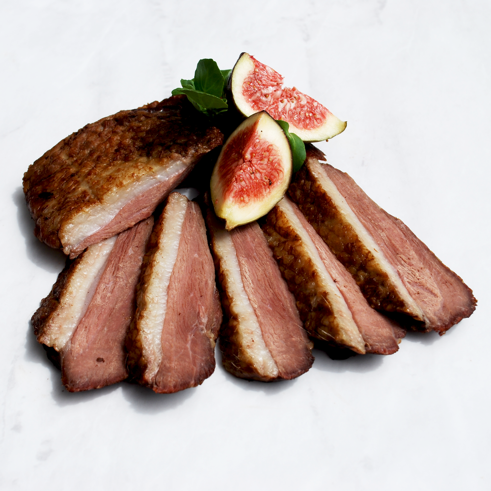 Sliced hot smoked duck breast on marble surface with fig segments and fresh watercress