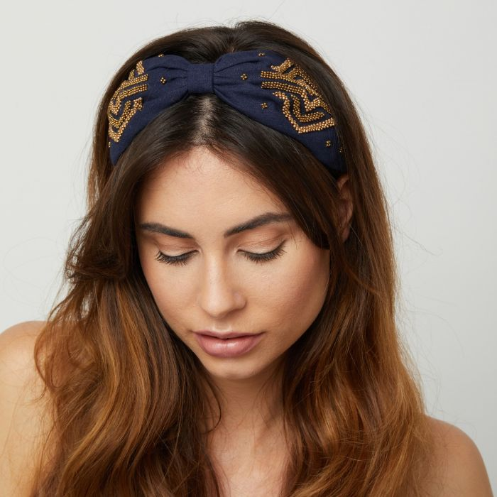 Beautiful Navy headband with gold coloured beaded art deco design.  Features a knot at the centre to draw focus from the wide fit.    Size  - One size