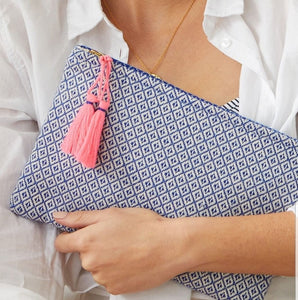 This clutch is made from woven cotton blend fabrics with handmade matching tassels and lined in a waterproof fabric, making it perfect to carry make up or take on holiday with your travel essentials.  Use as an evening clutch to brighten up a black outfit.  Colours are reversed on the back of the pouch   Size: 26.5 x 18 cm  Materials:  Cotton, Jute, Polyester & Acrylic