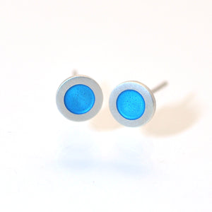 Small flat round ear studs with blue turquoise coloured enamel in the centre
