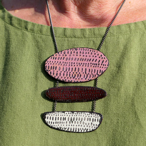 Necklace in three tiers. Pink then brown below that and buttermilk below that, all made from vitreous enamel with patterned texture. Hung on an oxidised silver chain