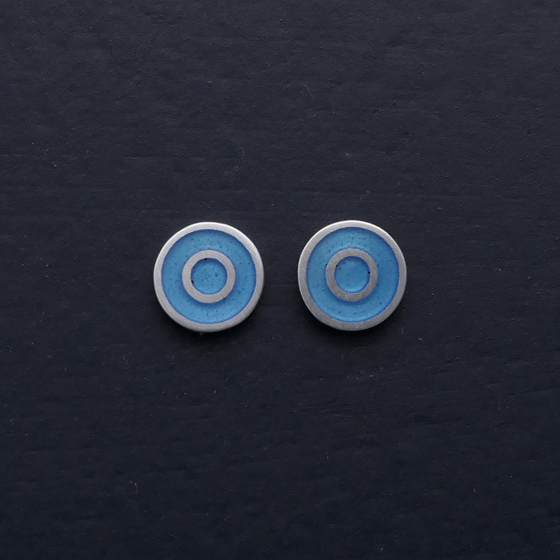 Small round silver ear-stud, concentric. Light blue