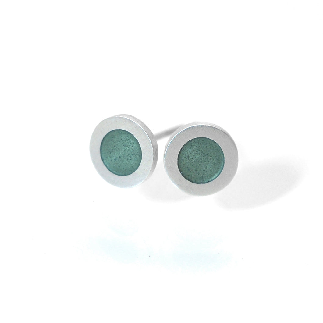 Small flat round ear studs with green grey coloured enamel in the centre