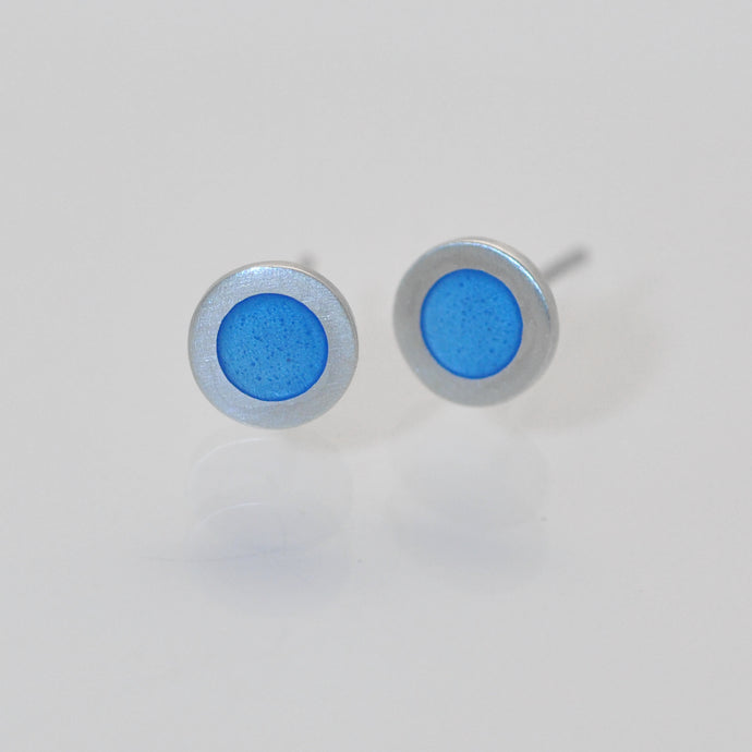 Small flat round ear studs with Light blue coloured enamel in the centre
