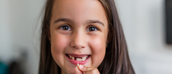 Child holding lost tooth