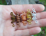 A set of 5 ombre dread beads in hand to show scale.
